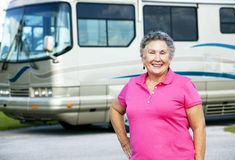 Senior Woman with Motor Home. Portrait of a pretty senior woman in front of her luxury motor home Stock Image