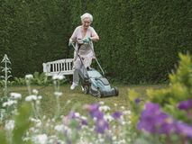 Senior woman mowing grass stock photos