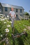 Senior woman mowing lawn Royalty Free Stock Image