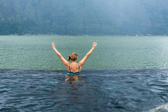 Senior woman in the nature swimming pool with amazing mountain background. Tropical island Bali, Indonesia. Stock Photography