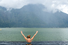 Senior woman in the nature swimming pool with amazing mountain background. Tropical island Bali, Indonesia. royalty free stock photography
