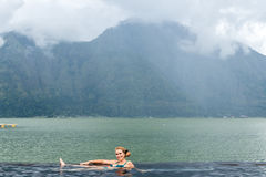 Senior woman in the nature swimming pool with amazing mountain background. Tropical island Bali, Indonesia. Stock Image