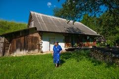 Senior woman near old wooden house Stock Photo