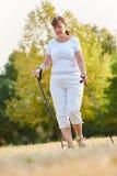 Senior woman during nordic walk Stock Images