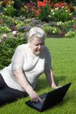 Senior woman with notebook in the garden Royalty Free Stock Image