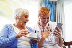 Senior woman and nurse using digital tablet Royalty Free Stock Photos