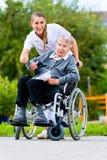 Senior woman in nursing home with nurse in garden Stock Image
