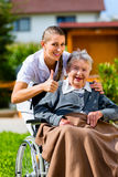 Senior woman in nursing home with nurse in garden Stock Image