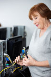 Senior Woman Observing Computer Cables Stock Photography