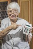 Senior woman with old calculator Royalty Free Stock Images