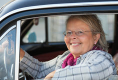 Senior woman in oldtimer car. Happy senior woman driving an oldtimer car Royalty Free Stock Image