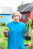 Senior woman with onion and lettuce Royalty Free Stock Image