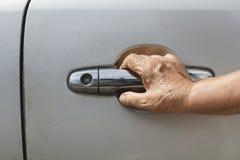 Senior woman open a car door. At parkinglot Royalty Free Stock Image
