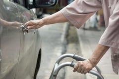 Senior woman open car door with walker. Stock Photos