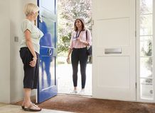 Senior woman opens door to female care worker on home visit royalty free stock photography