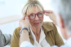 Senior woman in optical store. Senior woman trying new eyeglasses on, optical store Stock Photos