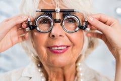 Senior woman in optician's office. Having examined sight stock photography