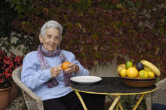 Senior  woman with a orange fruit Stock Photos