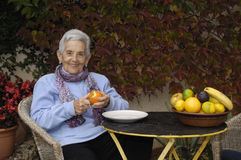 Senior  woman with a orange fruit Royalty Free Stock Photography