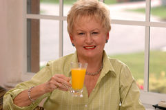 Senior woman with orange juice. A senior woman holding a glass of orange juice by a sunny window Royalty Free Stock Images