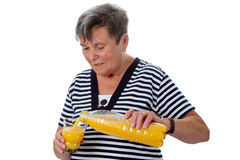 Senior woman with orange juice Stock Photography