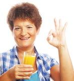 Senior woman with orange juice Stock Photography