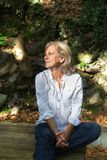Senior woman outdoors, joyness. Senior woman, 61 years old, wearing a shirt and jean, autumn season, nature background, sitting, lookiing away Stock Images