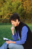 Senior woman outdoors thinking. Senior woman sitting in park studying her diary Royalty Free Stock Photos