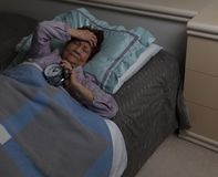senior woman in pain holding her alarm during sleepless night while in bed royalty free stock images