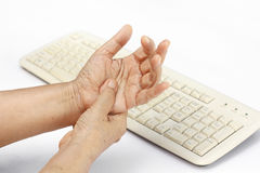 Senior woman painful finger cause use of keyboard Stock Photo