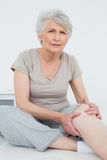 Senior woman with painful knee sitting on examination table Royalty Free Stock Images