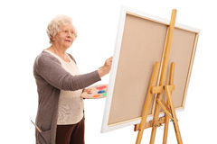 Senior woman painting on a canvas. Senior female artist painting on a canvas with a paintbrush isolated on white background royalty free stock photos