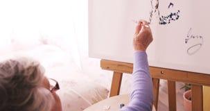 Senior woman painting on canvas stock video