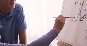 Senior woman painting on canvas stock video footage