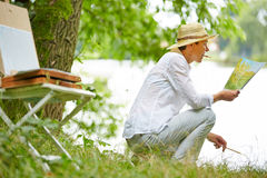 Senior woman painting picture in nature Royalty Free Stock Photo