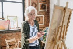 Senior Woman Painting Pictures in Art Studio. Waist up portrait of white haired senior woman holding palette painting pictures at easel in art studio standing royalty free stock image