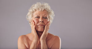 Senior woman pampering her face Stock Photo