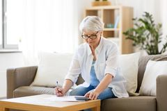Senior woman with papers and calculator at home. Business, savings, annuity insurance, age and people concept - senior woman with papers or bills and calculator stock photo