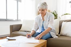 Senior woman with papers and calculator at home. Business, savings, annuity insurance, age and people concept - senior woman with papers or bills and calculator stock image
