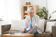 Senior woman with papers and calculator at home. Business, savings, annuity insurance, age and people concept - senior woman with papers or bills and calculator royalty free stock photo