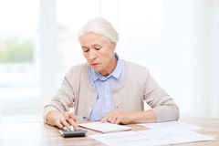 Senior woman with papers and calculator at home Royalty Free Stock Photo