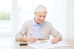Senior woman with papers and calculator at home. Business, savings, annuity insurance, age and people concept - senior woman with papers or bills and calculator royalty free stock photography