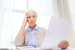 Senior woman with papers and calculator at home. Business, savings, annuity insurance, age and people concept - senior woman with papers or bills and calculator stock photography