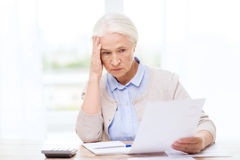 Senior woman with papers and calculator at home Stock Photography