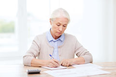 Senior woman with papers and calculator at home Royalty Free Stock Photos