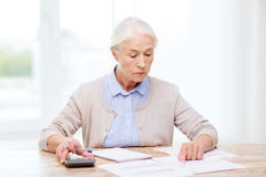 Senior woman with papers and calculator at home Stock Image