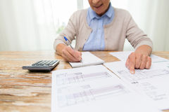 Senior woman with papers and calculator at home. Business, savings, annuity insurance, age and people concept - close up of senior woman with papers or bills and royalty free stock photo