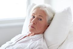 Senior woman patient lying in bed at hospital ward. Medicine, age, health care and people concept - senior woman patient lying in bed at hospital ward Royalty Free Stock Images