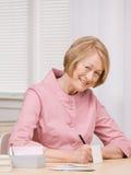 Senior woman paying bills at desk. Smiling senior woman paying bills with checks at desk Stock Photos