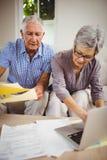 Senior woman paying bills online on laptop Royalty Free Stock Images